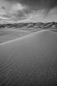 Clouds from a storm rolling through the Great Sand Dunes almost touch the top of the dunes. - Colorado Black and White Landscape Photograph