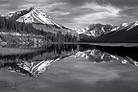 Only a small ripples disturbs the reflection of the mountains in the distance. - 777 Photograph
