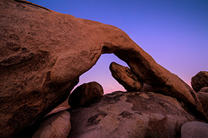 The sky takes on a deep purple hue over the natural arch in Joshua Tree National Park. - California Landscape Photograph