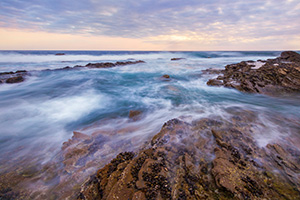 Waves wash around the rocks on the beach at Crystal Cove State Park, California while the sun sets in the distance. - California Landscape Photograph