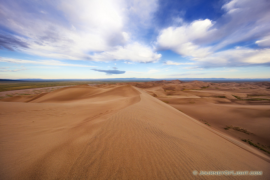 At Great Sand Dunes National Park and Preserve, dunes flow into the west as white clouds float high above. - Great Sand Dunes NP Photography