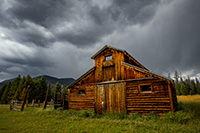 Under stormy clouds, a wooden barn sits in the Kawuneeche Valley on the western side of Rocky Mountain National Park in Colorado. - Colorado Landscape Photograph