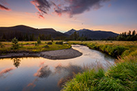 The sun sets behind the Never Summer Range as the Kawunechee River flows through the west side of Rocky Mountain National Park in Colorado. - Colorado Photograph