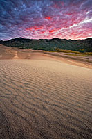 Early morning on the Great Sand Dunes after a stormy night brought clouds that reflected intense warm hues from the rising sun.  I had envisaged a photograph like this at the sand dunes for over a year, capturing the the texture of the dunes, the sweeping lines that lead to the Sangre de Cristo mountains, with a brillant sunrise. - Colorado Photograph