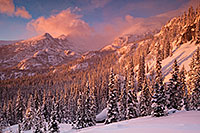 Sunlight illuminates the freshly fallen snow and the trees in the valley while Long's Peak is partially hidden by the blowing snow and clouds. - Colorado Landscape Photograph