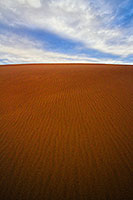 From the base of a tall dune looking skyward, clouds float above the dunes at Great Sand Dune National Park. - Colorado Landscape Photograph Photograph