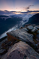Clouds gather in the valleys of Rocky Mountain National Park as the sun sets in the distance. - Colorado Photograph