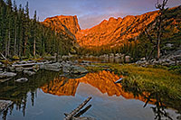 Still and peaceful, Dream Lake in Rocky Mountain National Park reflects an image of the majestic Hallett Peak while it glows red with the light of the rising sun. - Colorado Photograph