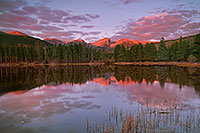 During a cool October sunrise, bright with alpenglow, the peaks of the continental divide, Powell Peak, Taylor Peak, Otis Peak, Hallett Peak, and Flattop Mountain are reflected in the calm waters of Sprague lake while underlit clouds hover overhead. - Colorado Photograph