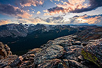 The setting sun streams through the clouds, illuminating the peaks of Rocky Mountain National Park and the valley below. - Colorado Photograph