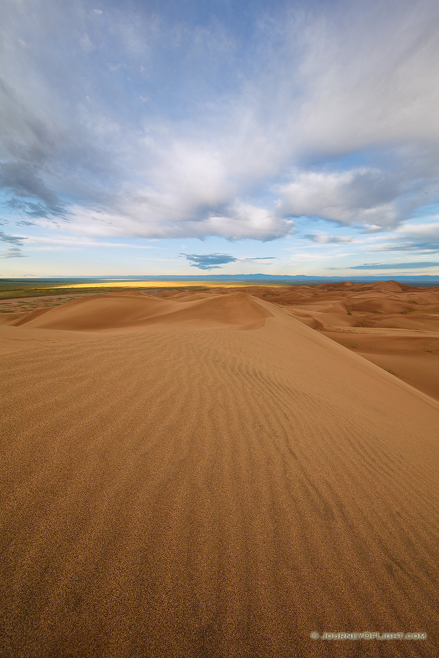 Dunes flow into the west at Great Sand Dunes National Park as white clouds lazily float above. - Great Sand Dunes NP Picture