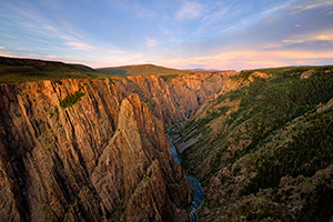 As the sun sets in the west in Black Canyon of the Gunnison National Park, the last glow of the day skims the canyon walls to the east. - Colorado Landscape Photograph