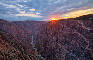 The last bit of sun hangs just above the canyon wall at Black Canyon of the Gunnison National Park on a cool summer evening. - Colorado Landscape Photograph