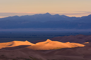 Light graces the tops of the Sand Dunes in the distance as the sun peaks over the Sangre De Cristo range. - Colorado Landscape Photograph