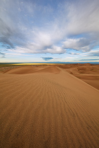 Dunes flow into the west at Great Sand Dunes National Park as white clouds lazily float above. - Colorado Landscape Photograph