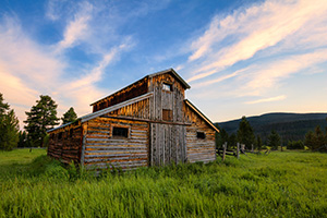A beautiful wooden barn sits in the Kawuneeche Valley on the western side of Rocky Mountain National Park in Colorado.  Clouds lazily floated by as the sun set behind the Never Summer Range in the distance. - Colorado Landscape Photograph