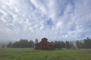 Fog engulfs the Kawuneeche Valley creating an eerie quiet near this old rustic barn in Rocky Mountain National Park. - Colorado Landscape Photograph