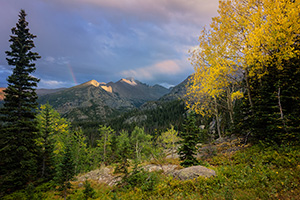 On a cool autumn evening sun strikes the peak of Long's Peak in Rocky Mountain National Park.  A faint rainbow briefly appeared as the storm moved over the mountain. - Colorado Landscape Photograph