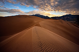 On a cool, autumn morning, silence reigned across the scenic Great Sand Dunes National Park, the quiet only occasionally broken by the sound of a breeze flowing through the dunes.  On top of one of the larger dunes, I captured the patterns of the sand as the dunes drift into one another, creating a path to the distant Sangre de Cristo Mountains.   Beyond the far peaks, the rising sun illuminates the cloud bank with a yellowish-orange tint. - Colorado Photograph