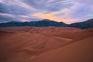 As the last of the light of the day diminishes at Great Sand Dunes National Park, a single set of clouds remain illuminated before quietly going dim. - Colorado Photograph
