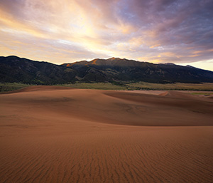 Sunlight streams through a pass in the Sangre de Cristo Mountains and illuminates the peak of Carbonate Mountain just southeast of the dunes at Great Sand Dune National Park. - Colorado Photograph