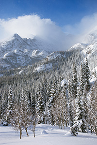 On the trail to Dream Lake, Long's Peak is obscured, encased in blowing snow and clouds in Rocky Mountain National Park, Colorado. - Colorado Photograph