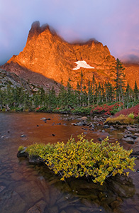One of my favorite lakes in Rocky Mountain is Lake Helene.  About 2 and a half miles from Bear Lake, this spot is nestled at the bottom of Notchtop Mountain.  On a September day, the leaves on the bushes have turned a bright crimson hue and the early morning fog begins to dissipate quickly as the the mountain glows with the advent of a new dawn.  It is serenity and peacefulness with only the rustling of the trees and the occasional chirp of a Steller�s Jay. - Colorado Photograph