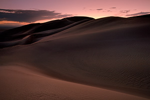 As I photographed this scene, I almost imagined myself in a foreign land as the sun dipped below the horizon.  The shapes of the dunes in this photo become abstract lines and patterns in the late dusk light. - Rockies Photograph
