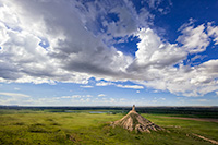 From a vantage point on a nearby bluff Chimney Rock glows in the light of the warm afternoon sun under a dark blue sky filled with clouds. - Nebraska Photograph