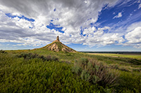 On a cool spring day, under a beautiful blue sky filled with puffy white clouds, Chimney Rock glows in the warm light of the afternoon sun. - Nebraska Photograph