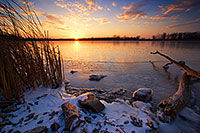 The warm setting sun shines brightly across the frozen lake before dipping below the horizon.  On a cold February evening in 2006 I ventured to DeSoto Wildlife Refuge looking to photograph the Bald Eagles that nest here in the winter.  What I found was a gorgeous sunset. - Nebraska Photograph