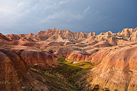 One of the things that I can say about visiting <a href='http://www.journeyoflight.com/journey12/photo-keyword-sort.asp?keywordselected=Badlands National Park'>Badlands National Park</a> in <a href='http://www.journeyoflight.com/journey12/photo-keyword-sort.asp?keywordselected=South Dakota'>South Dakota</a> is that the weather is almost always very dynamic when I am there.  I rarely have times when it is all sunny or all cloudy.  Usually, when the sun bursts forth there is some great color in the sky.  During the day clouds lazily float by and then in the afternoon I am often treated to a spectacular storm.  This image is from one such evening, a summer storm was rolling through and the sunlight was streaming through the clouds illuminating the badlands landscape. - South Dakota Photograph
