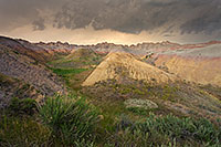 As a storm passes over Badlands National Park in South Dakota, the last light of the day illuminates a few distant clouds. - South Dakota Photograph