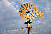 In rural Dixon County in Northeastern Nebraska a still windmill reflects the golden light of the rising sun against a cloudy sky. - Nebraska Photograph
