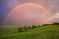 After an intense midwestern spring storm, from a Nebraska hilltop, an entire rainbow arches through the sky. - Nebraska Photograph
