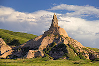 Clouds gather behind Chimney Rock as the glow of the late afternoon sun illuminates its western side. - Nebraska Photograph