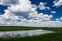 Clouds float lazily above a lake in the Sandhills of Nebraska. - Nebraska Photograph