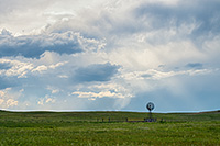 The sun peeks through a group of storm clouds illuminating a windmill deep within the Sandhills of Nebraska as storm clouds roll in the distance. - Nebraska Photograph