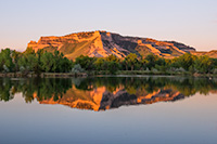 Glowing in the light of the recently risen sun, Scotts Bluff National Monument in western Nebraska is reflected in a small nearby lake. - Nebraska Photograph