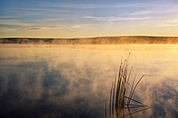 One of the most expansive and uninhabited areas of Nebraska also holds expansive beauty.  The Oglala National Grasslands in northwestern Nebraska represent some of the last native grasslands in the United States.  On a cool September morning a few years ago, I ventured out to the Meng Reservoir and captured the morning sun hitting the mist rising from the water.  The only sound was ducks quacking the distance welcoming the new day. - Nebraska Photograph