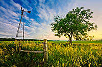 An old windmill and fence are the only company to a single tree on the eastern Nebraska plains. - Nebraska Photograph