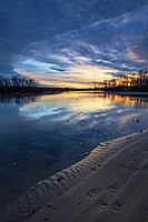 Paw prints from a raccoon are illuminated on the shore as the sun rises over the Missouri River at Ponca State Park in northeastern Nebraska. - Nebraska Landscape Photograph