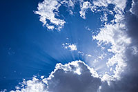 Sunbeams radiate from behind a cloud in the deep azure sky at Valentine National Wildlife Refuge, Nebraska. - Nebraska Photograph