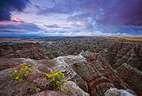 On a cool morning, the smell of a past rain fills the air.  The sunrise illuminates the passing storm clouds at Badlands National Park, South Dakota. - South Dakota Photograph
