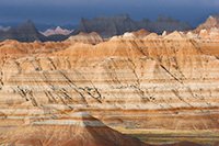 As a storm clears over the badlands light from the sun illuminates the rock formations while the dark clouds still dominate the sky in the distance. - South Dakota Photograph