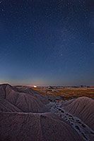 Stars fill the night sky while a train waits on the horizon at Toadstool Geologic Park near Chadron in western Nebraska. - Nebraska Photograph