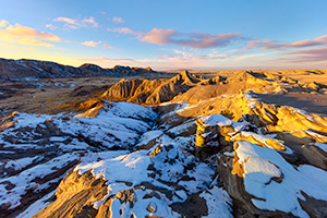 Scenic landscape photograph of sunset at Toadstool Geologic Park in western Nebraska after snow. - Nebraska Photograph