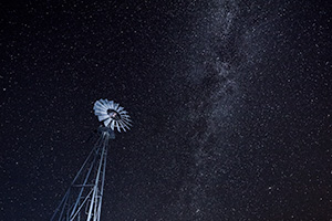A Nebraska landscape scenic photograph of a windmill under a night sky with lots of stars. - Nebraska Photograph