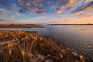 Bright puffy clouds float across the sky as the morning sun rises over the Missouri at Ponca State Park in northeastern Nebraska. - Nebraska Photograph