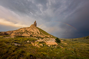 A scenic landscape Nebraska photograph of a rainbow over Chimney Rock in western Nebraska. - Nebraska Photograph